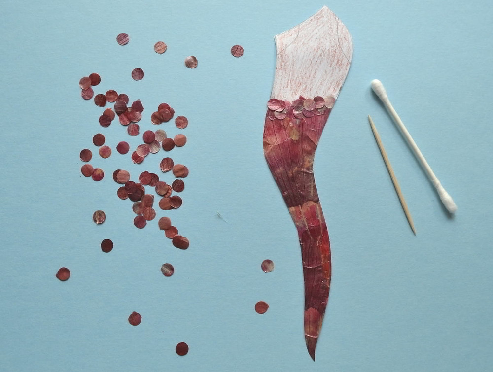 Toothpick, cotton swab, confetti made of red onion skin, a detail of figure of Mermaid for Pressed Plant Art are lying on the blue paper.