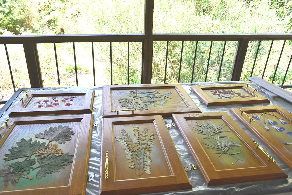 Doors of wooden cabinets with dried pressed plants. Pressed Flower Crafts.