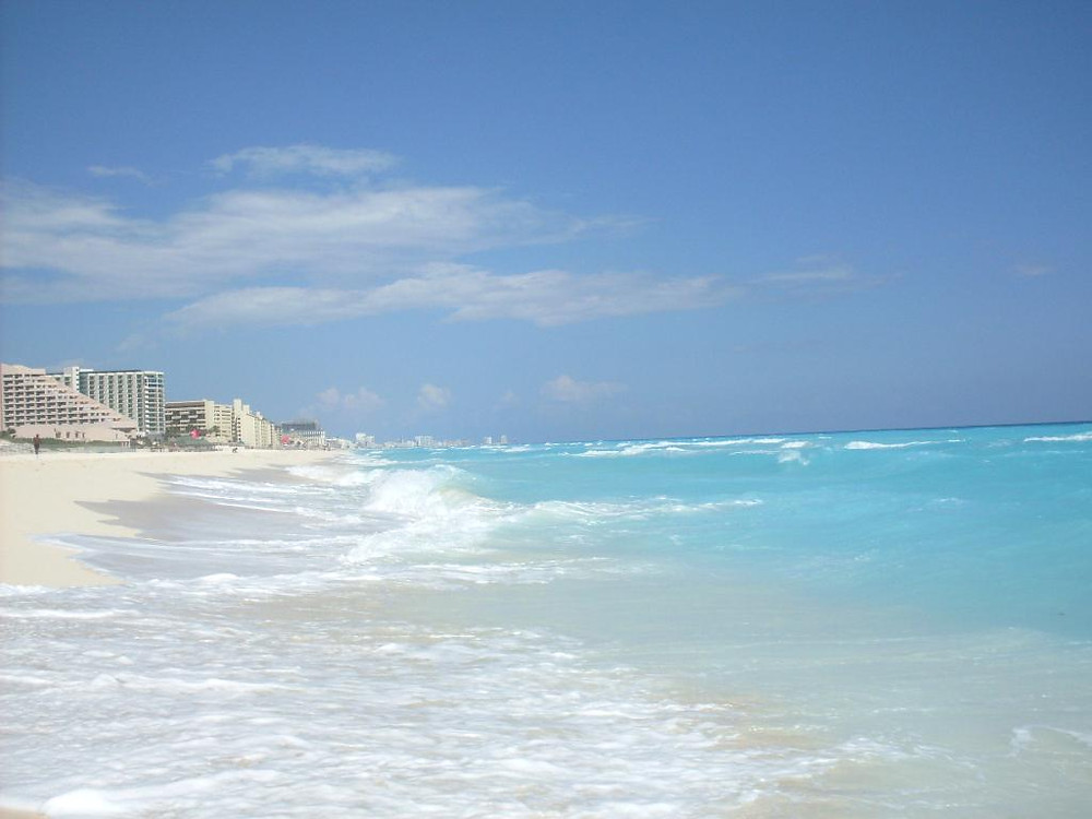 Coastline in Cancun, Mexico with some buildings. The seawater is lights turquoise. The sky is clear and blue.