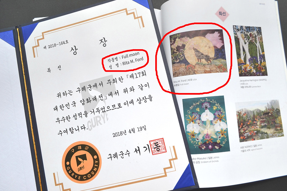 "Page of diploma from South Korea showing the name of art ""Full moon"" and name of artist Rita Ford. Page of printed catalog of exhibition in South Korea with the picture of Pressed Plant Art ""Full moon""."