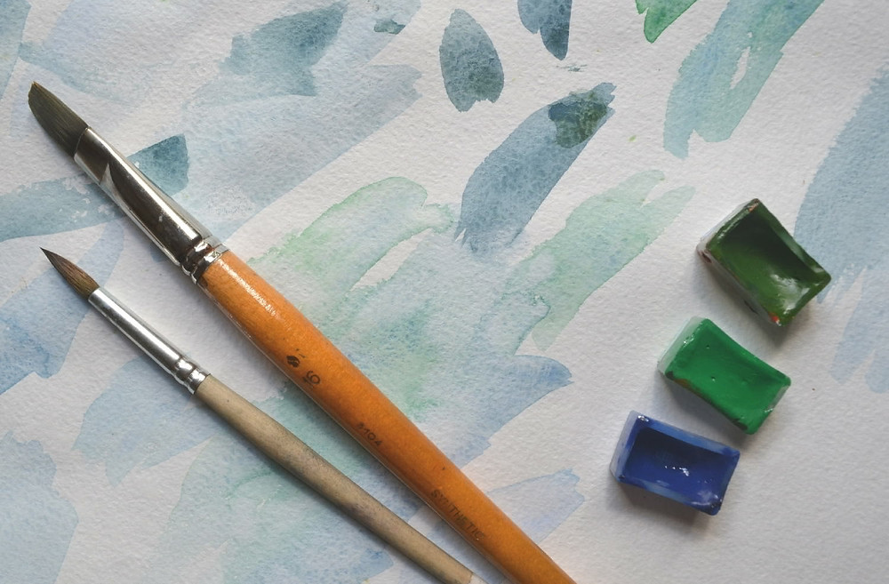A watercolor paper. Brushes and watercolor paints lying on the watercolor paper with watercolor.