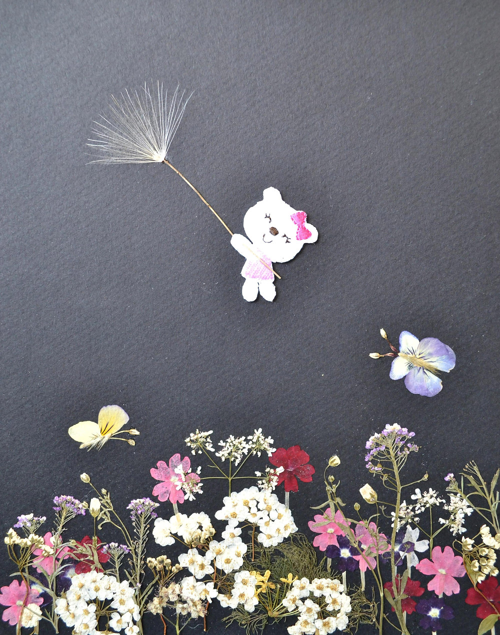 """Pressed Plant Art """"Fly"""". A happy pussycat is flying above flowering summer meadow holding a piece of thistle fluff in its paws. Butterflies are flying above flowers."""