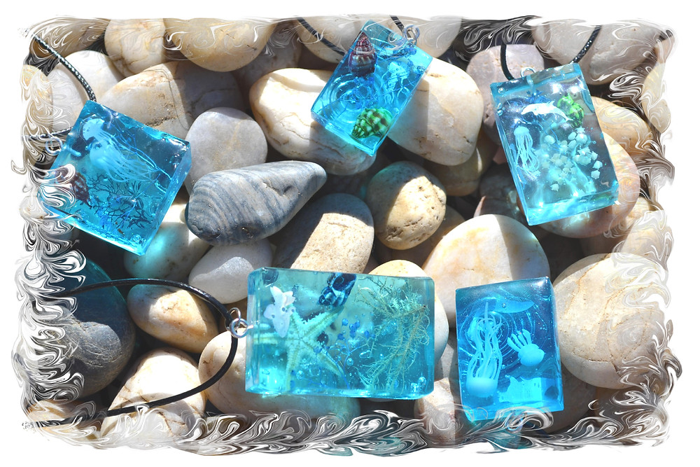 Resin pendants with something inside what imitates Marine life such as fish, Jellyfish, Starfish, seashells, corals, seaweeds and sea plants. Pendants are lying on stones.