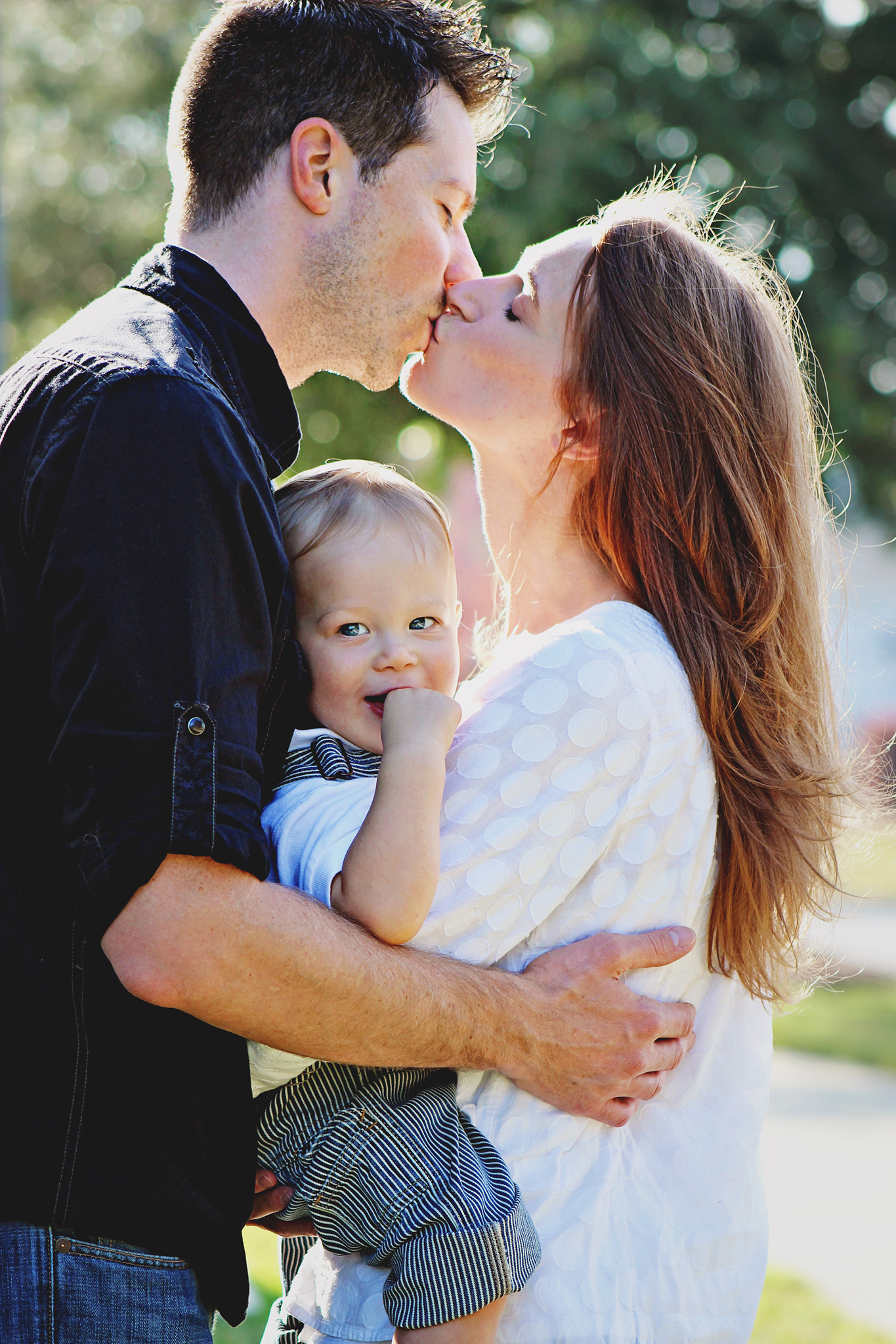 husband wife kissing baby birthday