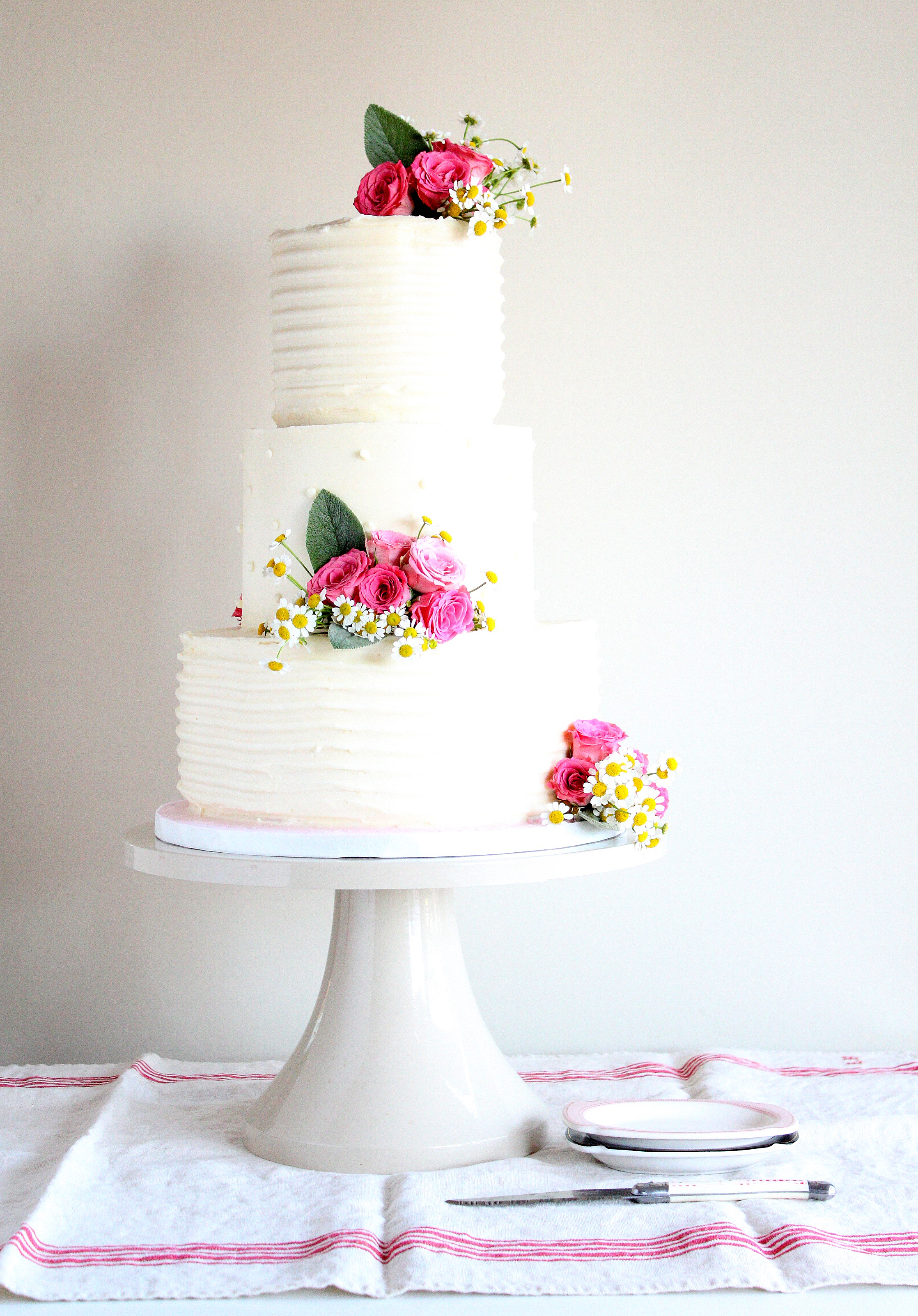 Vintage Romance Wedding Cake with pink roses, chamomile, and buttercream icing