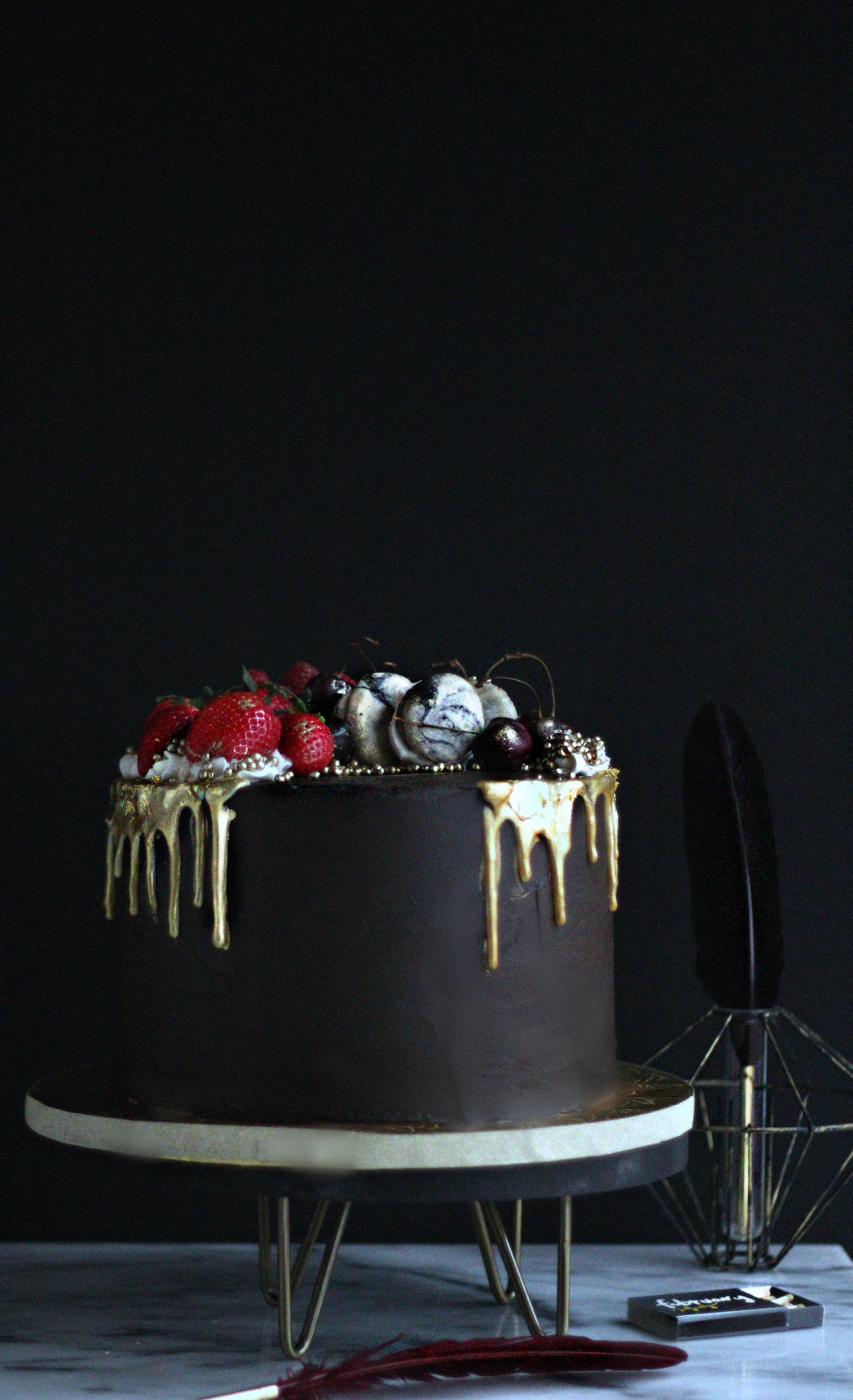 New moon black truffle birthday cake with gold drip and fruit crown side view e