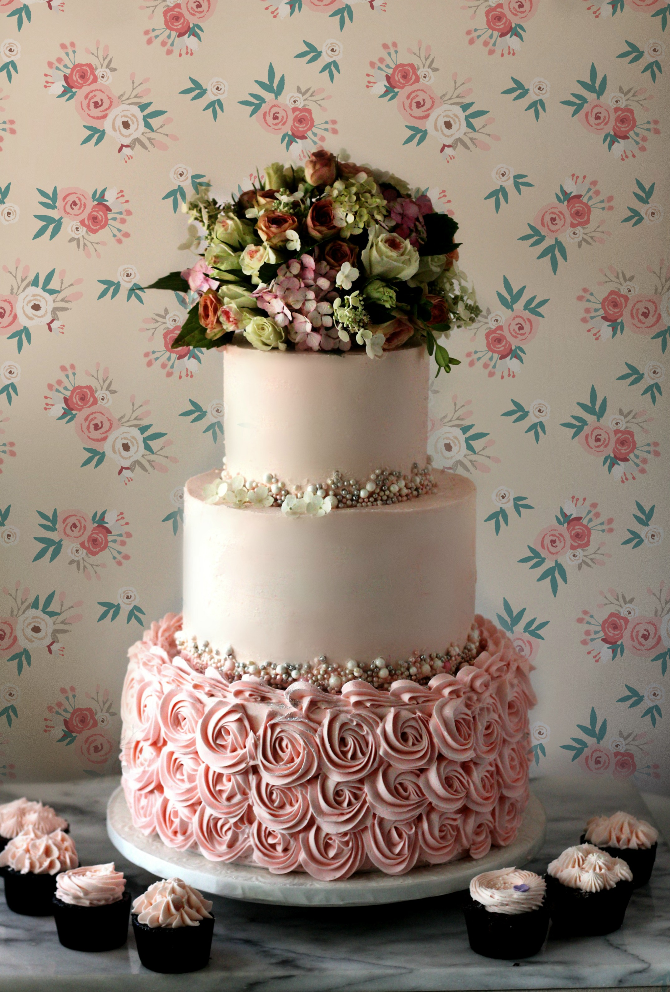 pink rosettes ombre all buttercream cake with fresh floral topper roses hydrangea floral wall paper