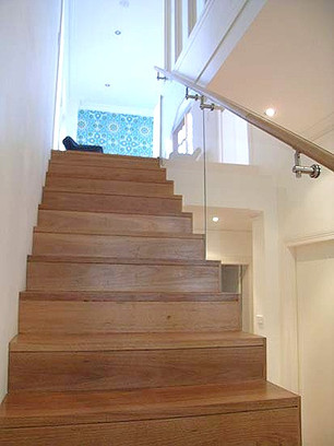 Timber stairs with glass balustrades and timber handrails by Budget Stairs