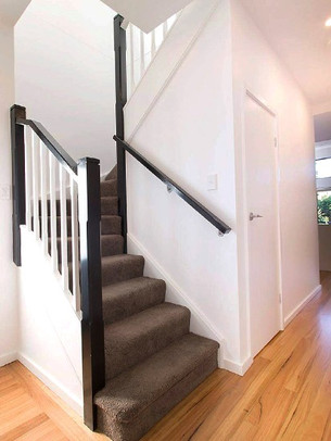 Black and white timber staircase design with carpeted stairs by Budget Stairs