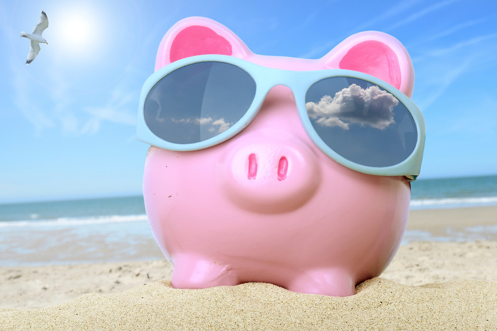 Piggy bank on the beach - Vacation Saving Tips
