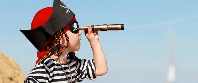 Child playing pirate outside beach