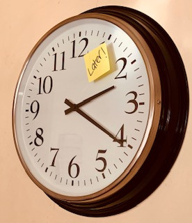 Photo of a wall clock with a post it note saying 'later' on it.
