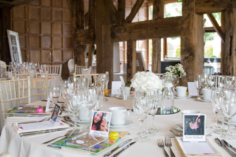 Old Brook barn, reception room with table favours & personalised polaroid name places