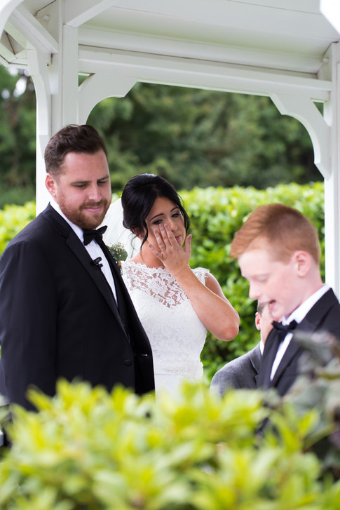 Bride & Groom listen to their son giving a reading during the ceremony whilst the bride sheds a tear