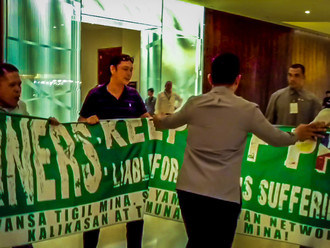 ACTIVISTS STORM MINING CONFERENCE