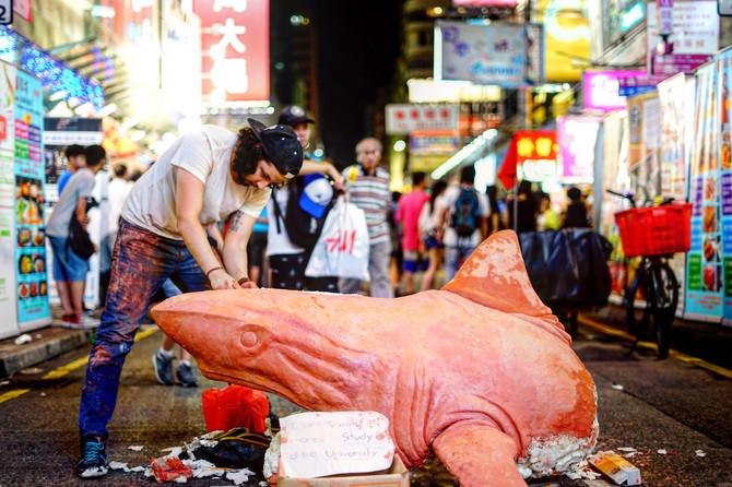 一把小刀,一隻橙紅色發泡膠鯊魚;旺角街頭,一名長髮外國人。