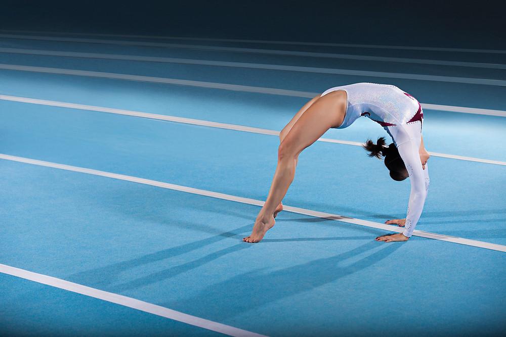 Gymnast doing back bend on mat