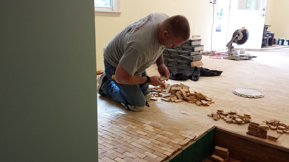 Jason Shepherd doing the back and knee breaking work of installing the end grain wood tiles on the kitchen sub-floor using the Bostik Adhesive.  Copyright 2015 Marla Baxter Sanderson - SockOnARooster.com