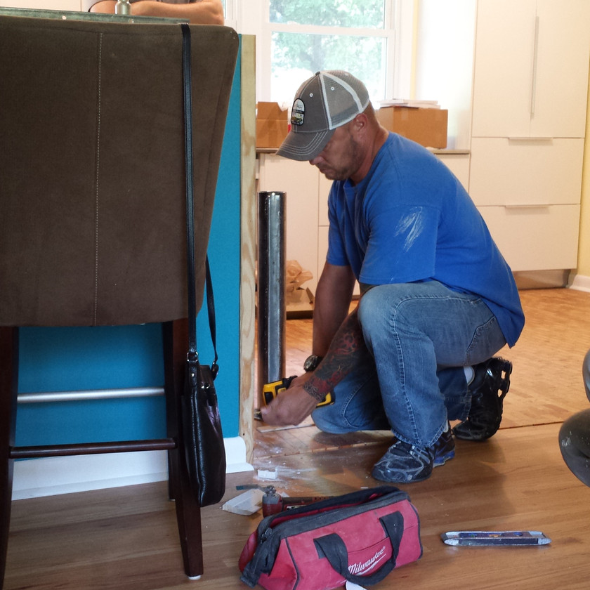 Jason installing a 2 x 6 to the half wall so that it will properly support the cantilevered guitar shaped table. Copyright 2015 Marla Baxter Sanderson - SockOnARooster.com
