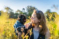 Griffon dog with lady within farm shrubs at sunset