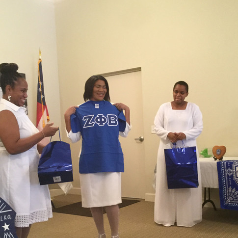 Soror Porter showing some of her induction gifts with Sorors Tamara Ragsdale and Tameka Mitchem