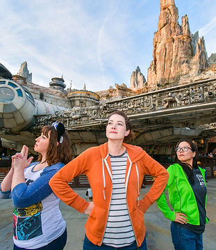 Three people posing in front of the Millennium Falcon at Star Wars: Galaxy's Edge