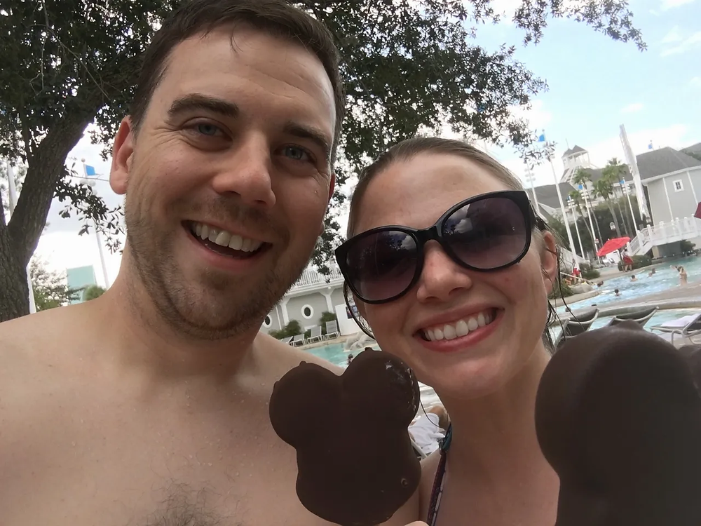 2 people eating a Mickey Ice Cream Bar by the Stormalong Bay Pool at Disney's Beach Club Resort