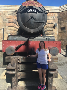 One person in front of the train engine for the Hogwarts Express from Harry Potter