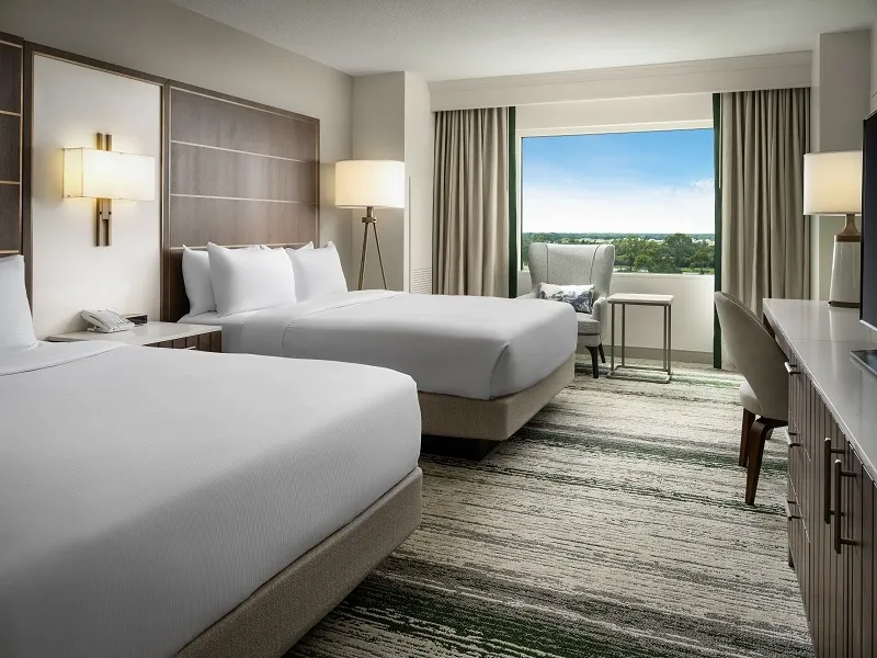 Two Queen Beds in a hotel room and view of a golf course at the Hilton Bonnet Creek Resort at Walt Disney World