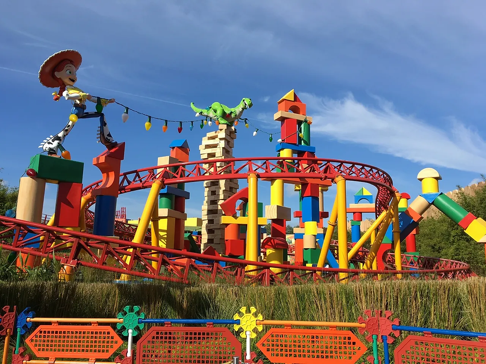 Roller coaster tracks from Slinky Dog Dash with oversized toys displayed in Andy's Backyard from Toy Story