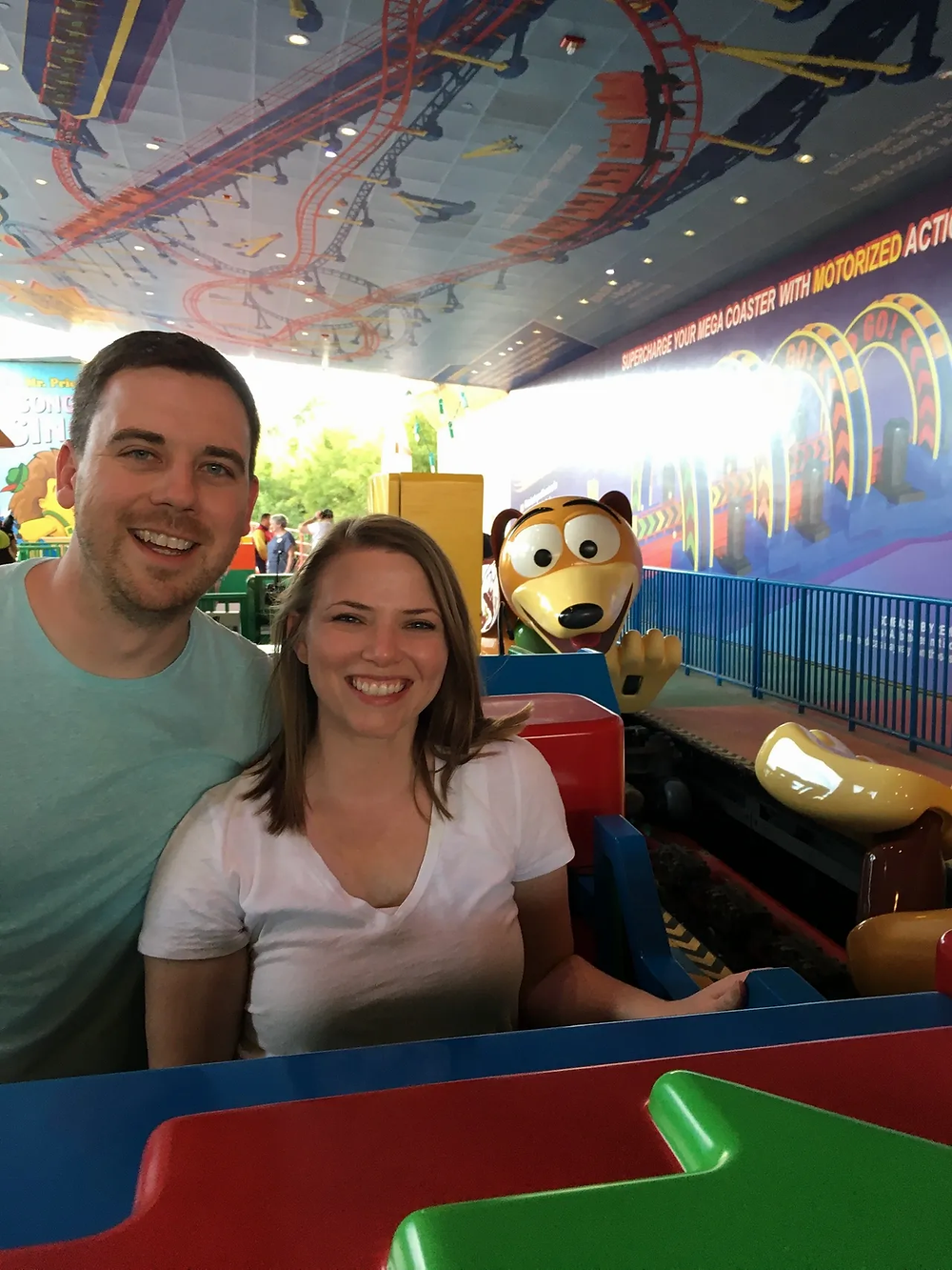 2 people in the boarding area for the roller coaster Slinky Dog Dash in Toy Story Land at Disney's Hollywood Studios