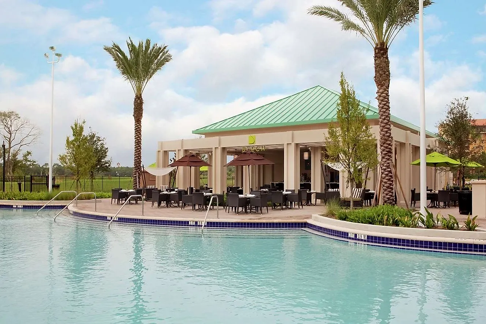 Pool bar overlooking swimming area with seating at Hilton Bonnet Creek Resort