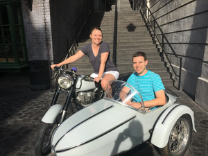 Two people sitting in Hagrids Magical Motorbike, outside Gringotts bank in Diagon Alley