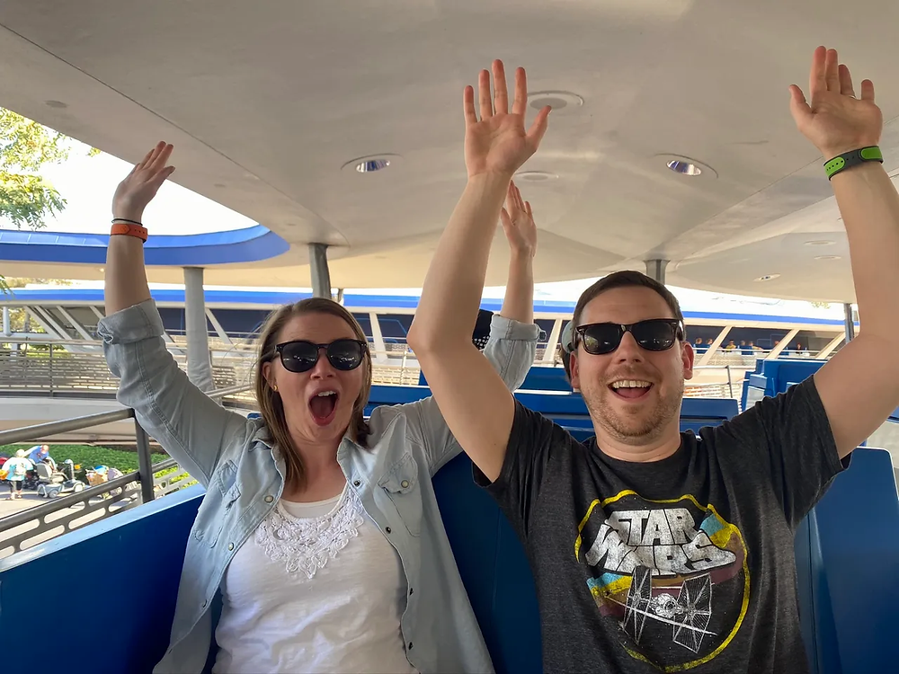 Two people riding the People Mover ride in Tomorrowland at Magic Kingdom in Disney World