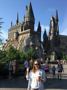 Woman standing in front of Hogwarts Castle drinking a Butterbeer from Harry Potter