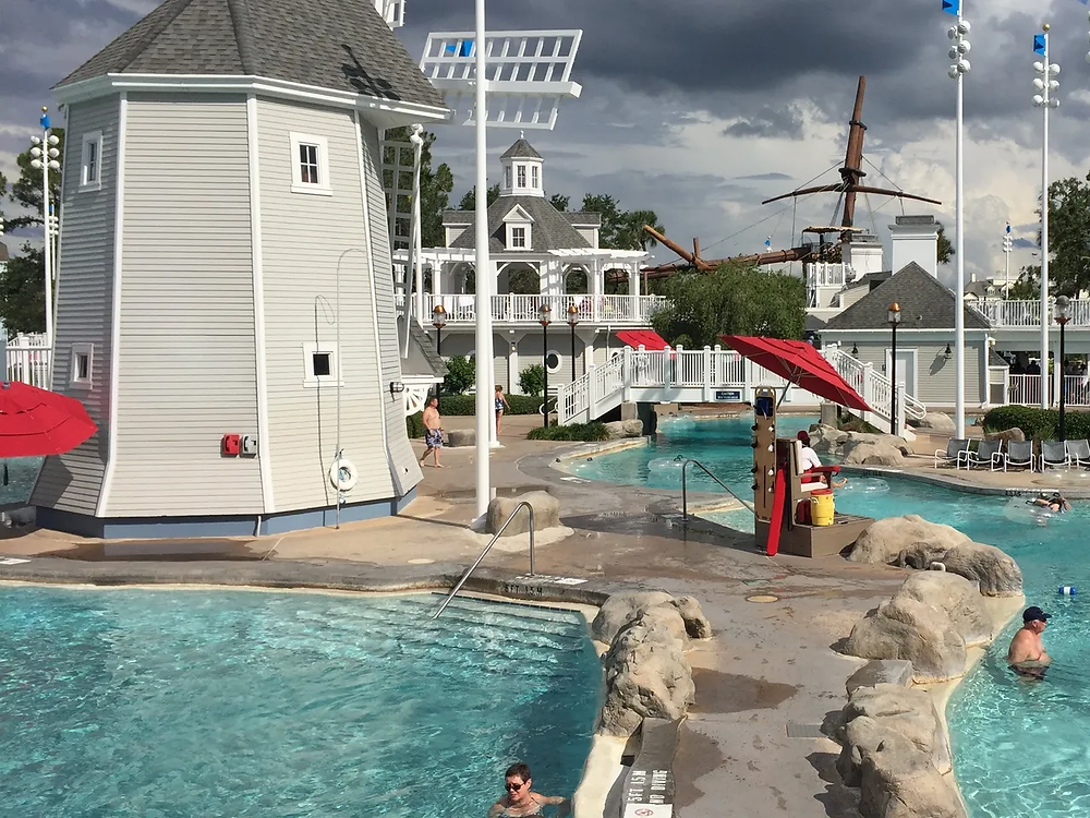 View of pool with lazy river, multiple entrances and bridges over the water. Also there is a lighthouse in the middle of the swimming area.
