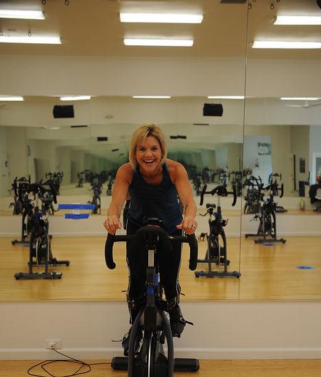a woman riding a stationary bike