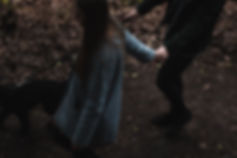 moody cinematic reportage photo of a couple walking and holding hands with their dog