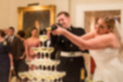 bride and groom powering champagne tower at their wedding reception