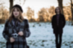 artistic couples engagement portrait with the girl in focus and the guy blurry in the background