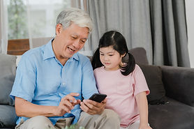 asian-grandparents-granddaughter-using-m