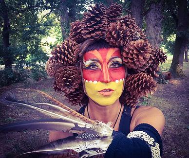 Maquillage tribal , coiffe en pignes de pins , costume en plume et coquillages . Danseuse FanFy Garcia