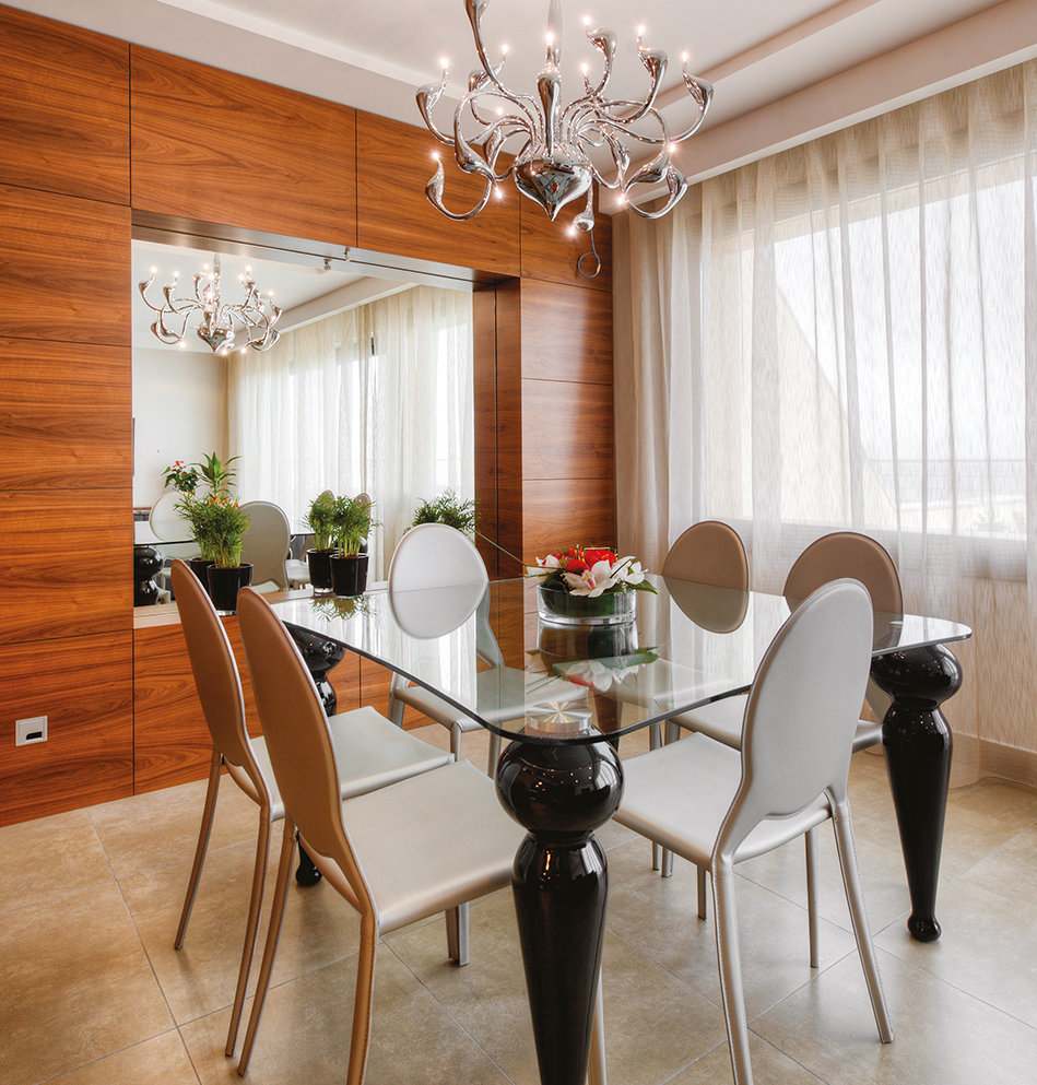 The dining room is elegantly furnished with a glass-topped table, a chandelier and some striking wood paneling.  The dining room's mirror also cleverly conceals a home theatre system. © Alan Carville