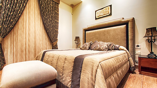 The master bedroom's main attraction is the luxuriously upholstered bed and accompanying pouffe.