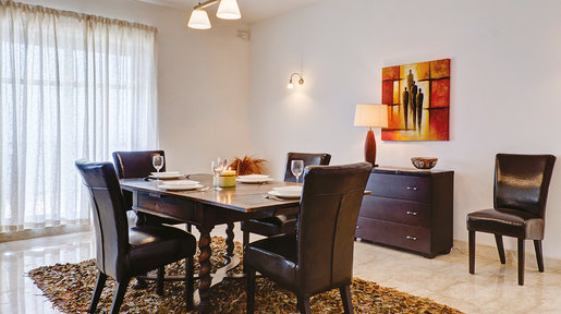 Dark leather upholstered chairs offer a stylish modern touch nicely complementing the dark hues of the old wood table. © Alan Carville