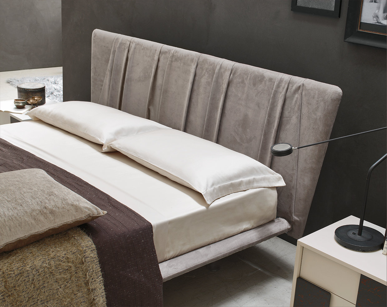 The velvety effect of the nubuck envelopes the bed and the space. The exclusive pleating technique used elegantly interprets oldfashioned style creating a classy headboard.
