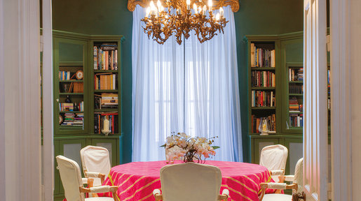 Dining room/Library – Bookshelves and mirrored cupboards were designed to contain the collection of books. To lighten the room, linen-style curtains sheers hang under a 19th century gilt pelmet. A French brass chandelier hangs over the table. Specialist lighting allows for 'stars' to glow down from the ceiling at night. © Alan Carville