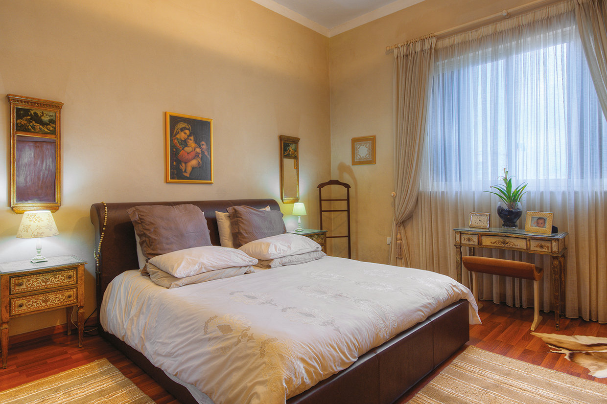 The master bedroom is a large room furnished with a contemporary bed with a leather headboard but also with a very pretty trio of Florentine antiques. © Alan Carville