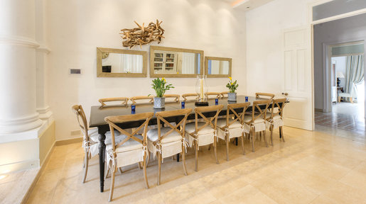Modern black dining table with storm candle and nightlights for evening dining is complemented by bentwood chairs. An unusual driftwood sculpture of seagulls hangs over 3 Moroccan mirrors. © Alan Carville
