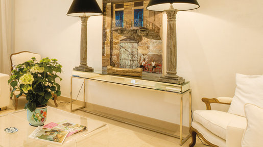 Modern white sofas and acrylic coffee tables from England. The mirrored glass console table and tall lamps, lighting an oil painting by Peter Heywood, were all purchased in Malta. © Alan Carville
